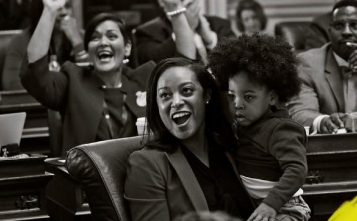 Del. Jennifer Carroll Foy holds her son, Alex Foy, as she and Del. Hala Ayala, D-Prince William, back, celebrate the passage of the Equal Rights Amendment in the House chambers at the Capitol, Jan. 27, 2020, in Richmond, Va.   PHOTO: STEVE HELBER, AP, ILL