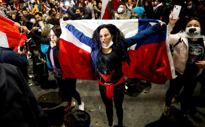 A woman holds a Chilean flag in Valparaiso last year. In a referendum in October, Chileans voted by a 79% landslide majority in favor of a popularly elected citizen assembly with gender parity. Photograph: Rodrigo Garrido/Reuters