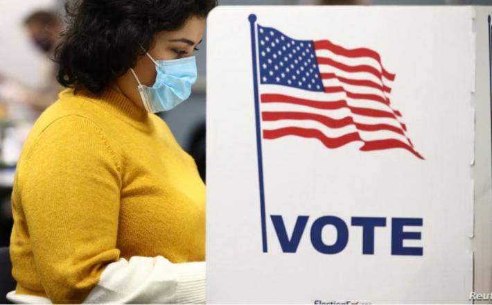 A woman fills in a ballot for the 2020 U.S presidential election in Fairfax, Virginia, November 3, 2020.