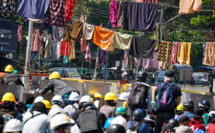 Protesters against the military coup in Myanmar are surrounded by women's clothes which have been hung in the streets to keep soldiers and police away [Stringer/Anadolu]