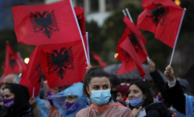 A woman looks on as people wave Albanian flags during a Socialist Party election rally in Tirana, Albania April 22, 2021. REUTERS/Florion Goga