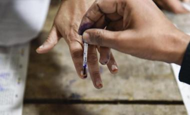 A polling official applies indelible ink on the finger of a voter. (Photo | PTI)