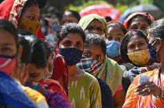Women wait to cast their ballots during the fifth phase of West Bengal's state legislative assembly elections, 17 April 2021 in Kolkata (Dibyangshu Sarkar/AFP via Getty Images)